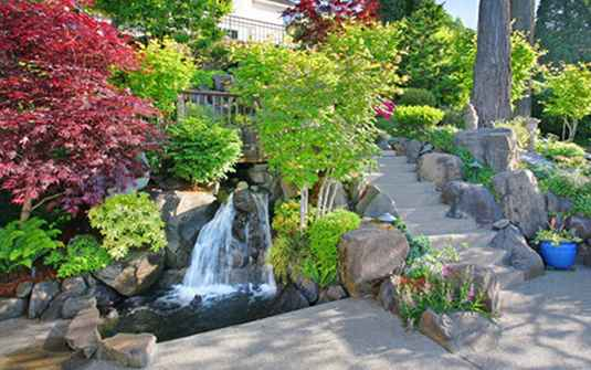 Residential home front lawn landscape with waterfall and trees
