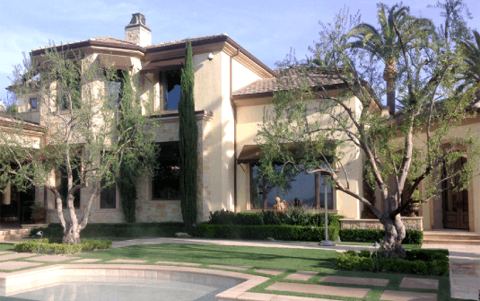 front yard of los angeles estate home with trimmed trees